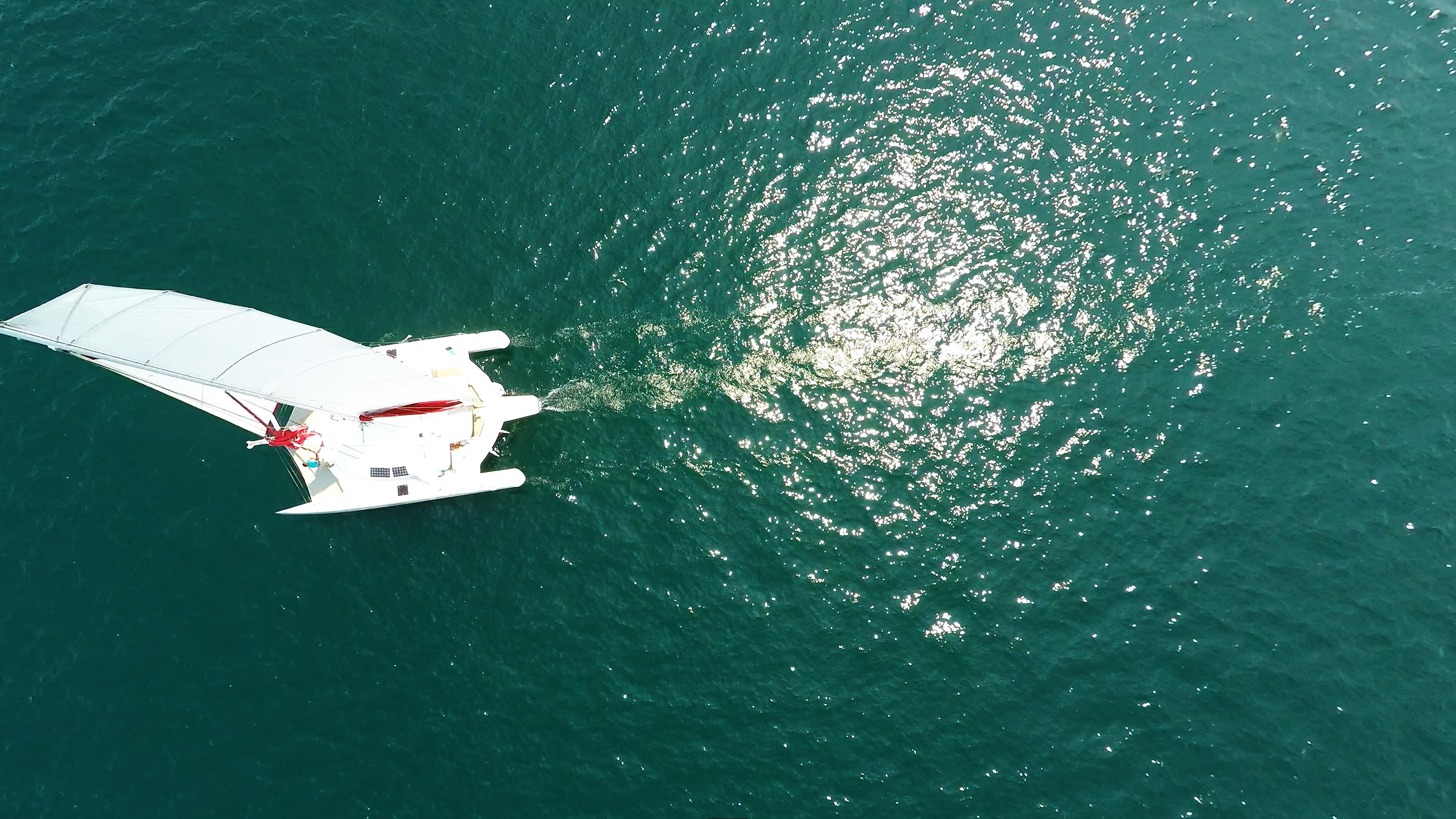 foto aerea nadir sole riflessa trimarano veleggiare mare