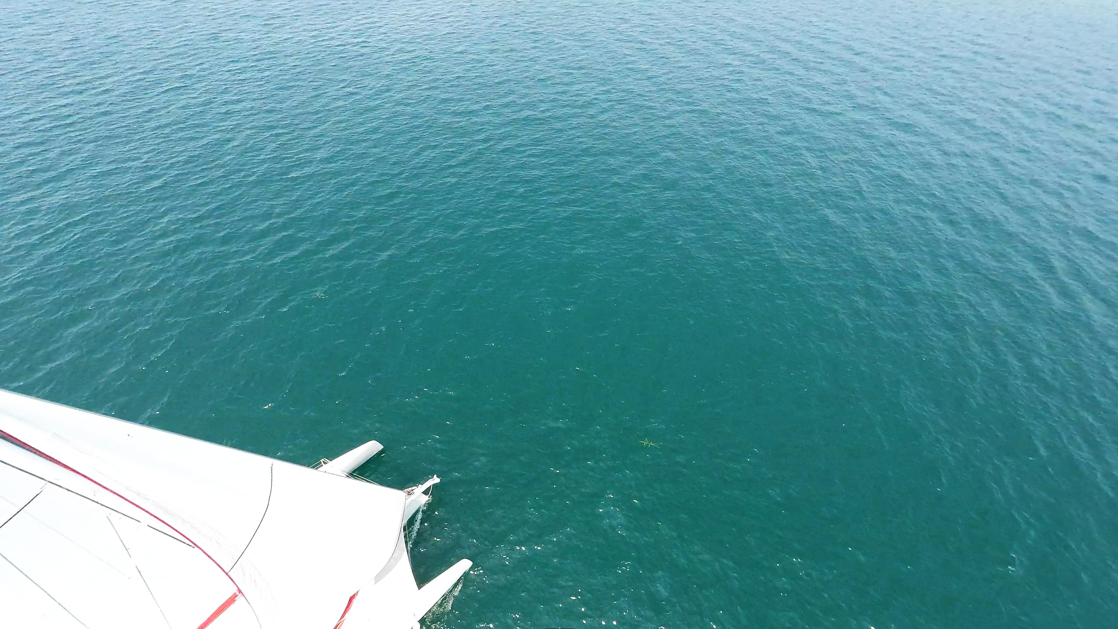 prua di multiscafo yacht sul blu-verde mare