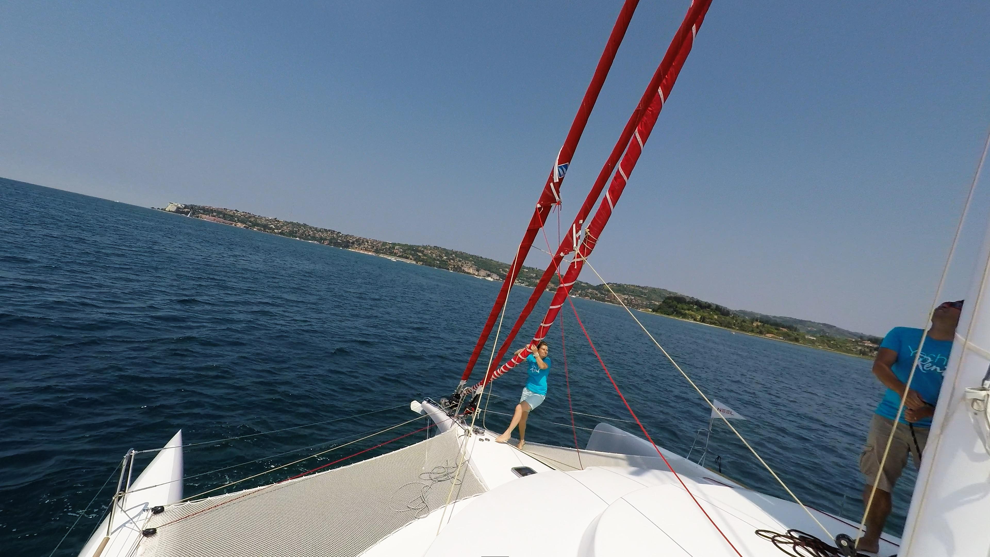 equipaggio rimuovendo gennaker dalla prua di trimarano  a vela yacht
