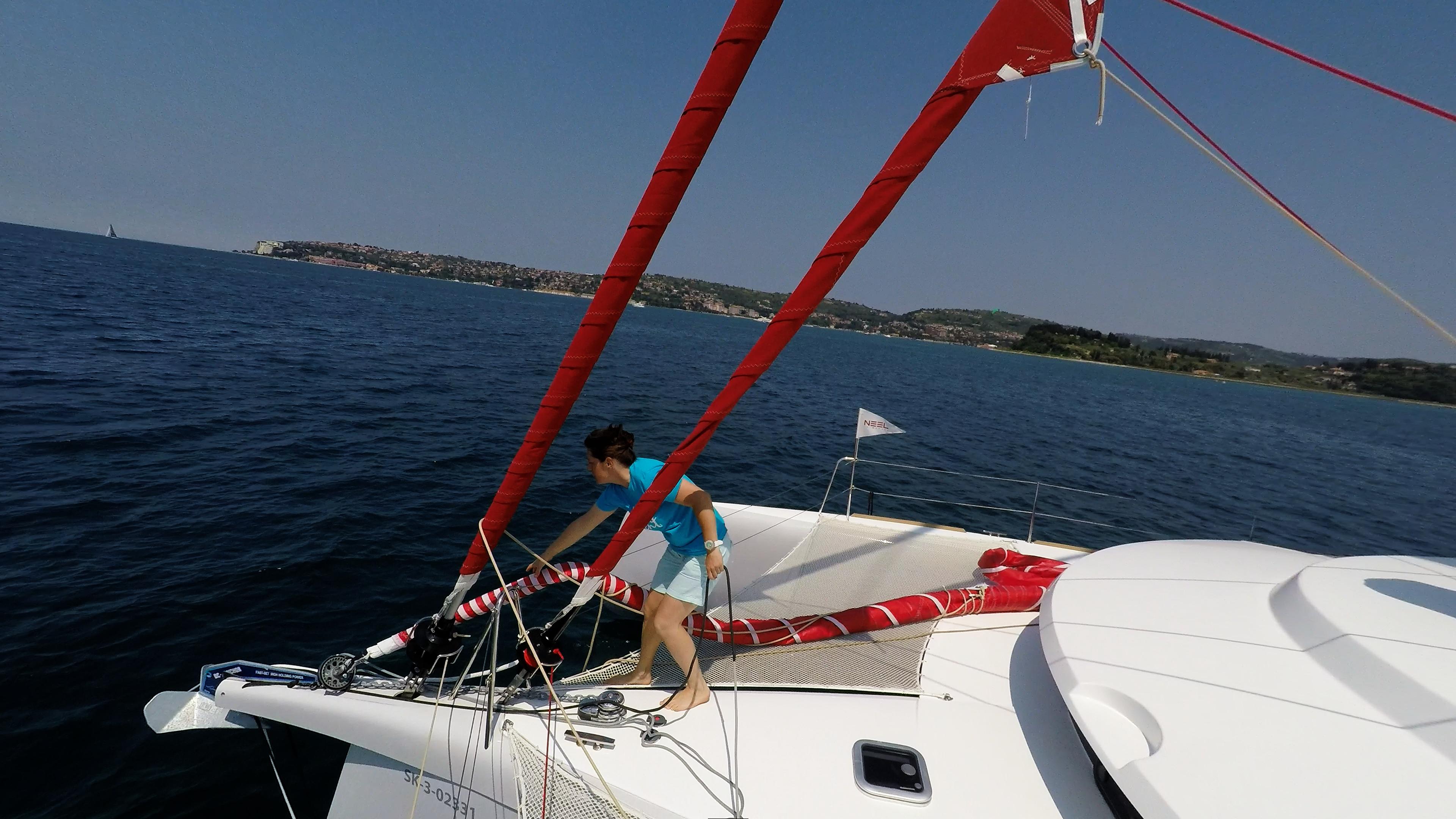 ragazza rimuovendo gennaker dalla prua della barca a vela trimarano neel 45