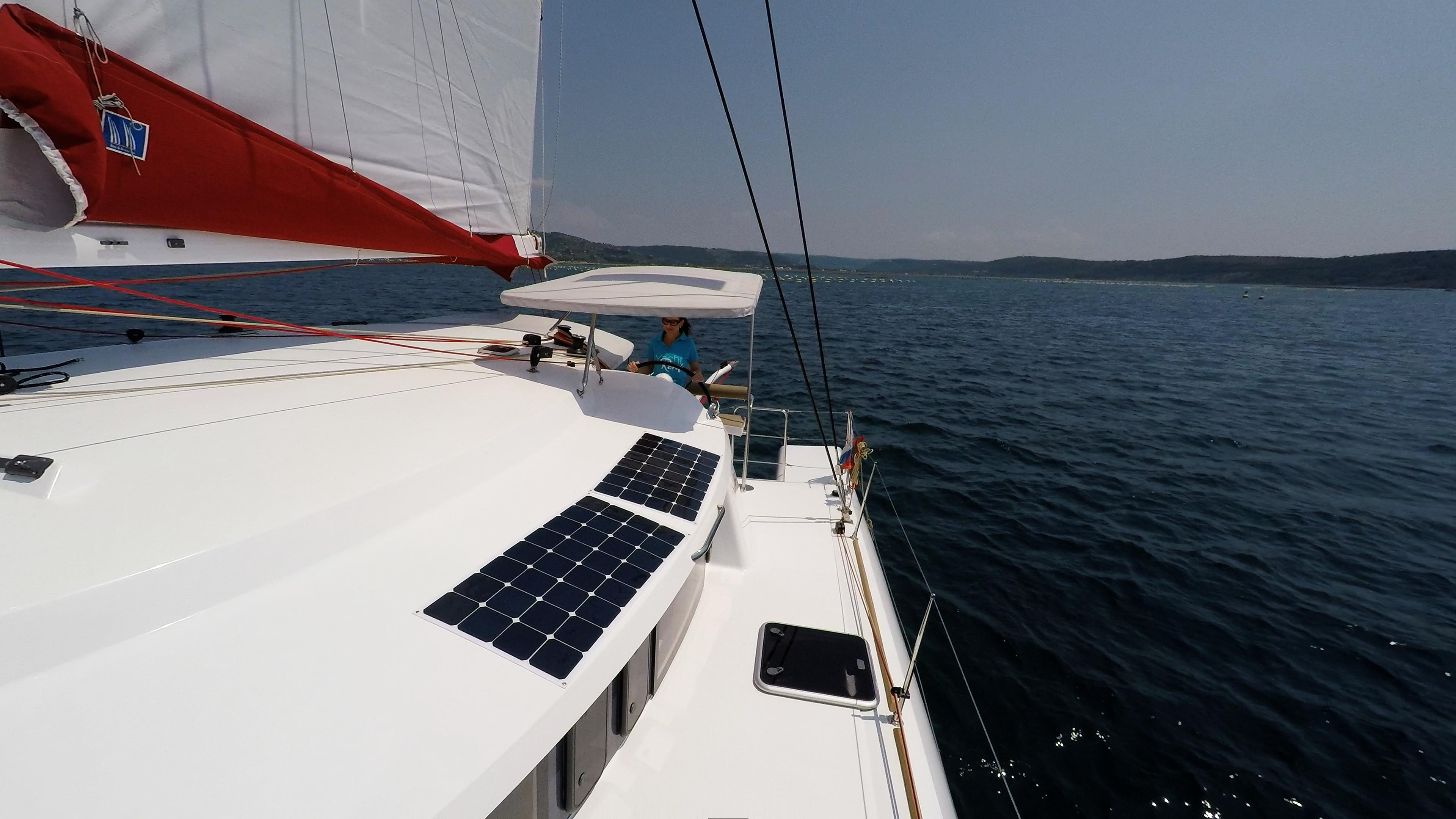 ragazza in skipper cockpit ruota del timone barca a vela trimarano