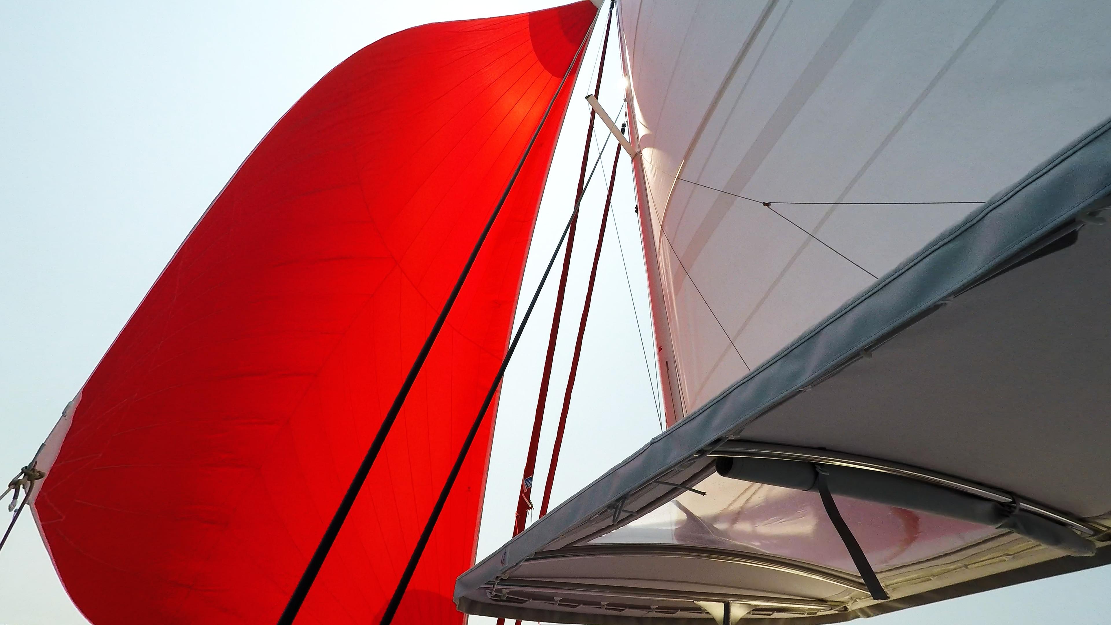 rosso gennaker e bianco mail vela over cockpit cima sul trimarano neel 45