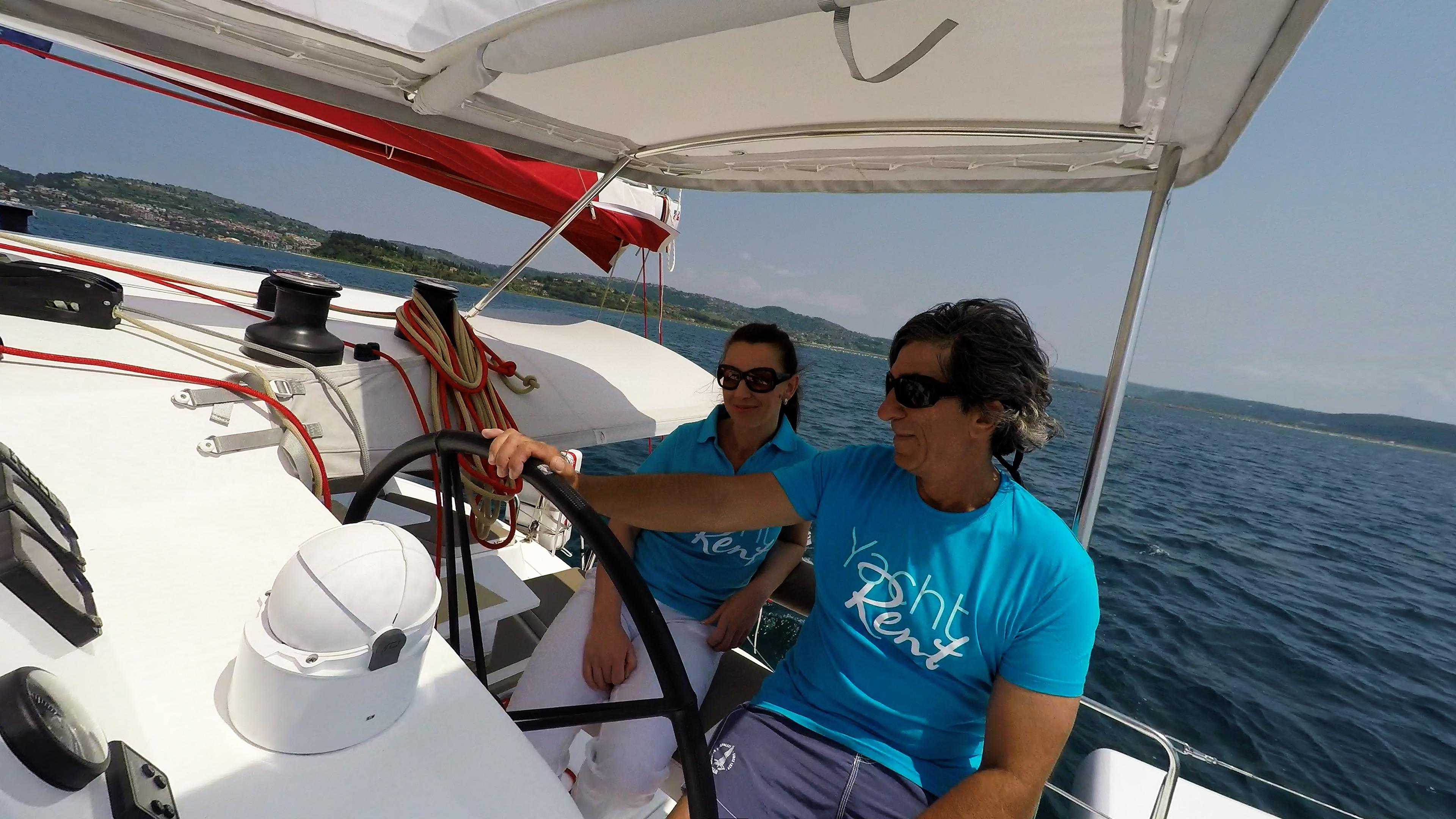 skipper e ragazza behind ruota del timone di trimarano  neel 45 yacht 2