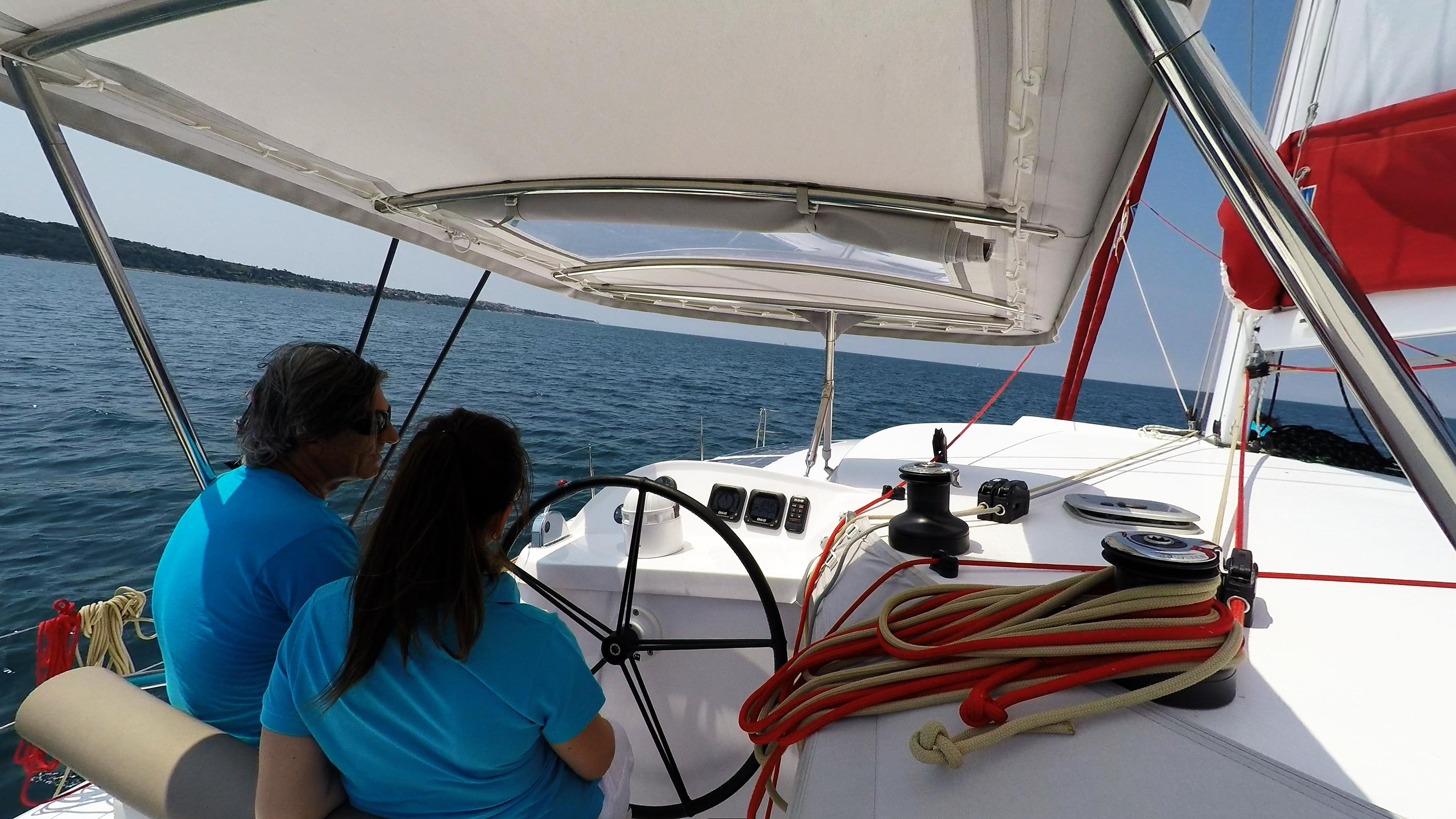 skipper e ragazza behind ruota del timone di trimarano  neel 45 yacht 4