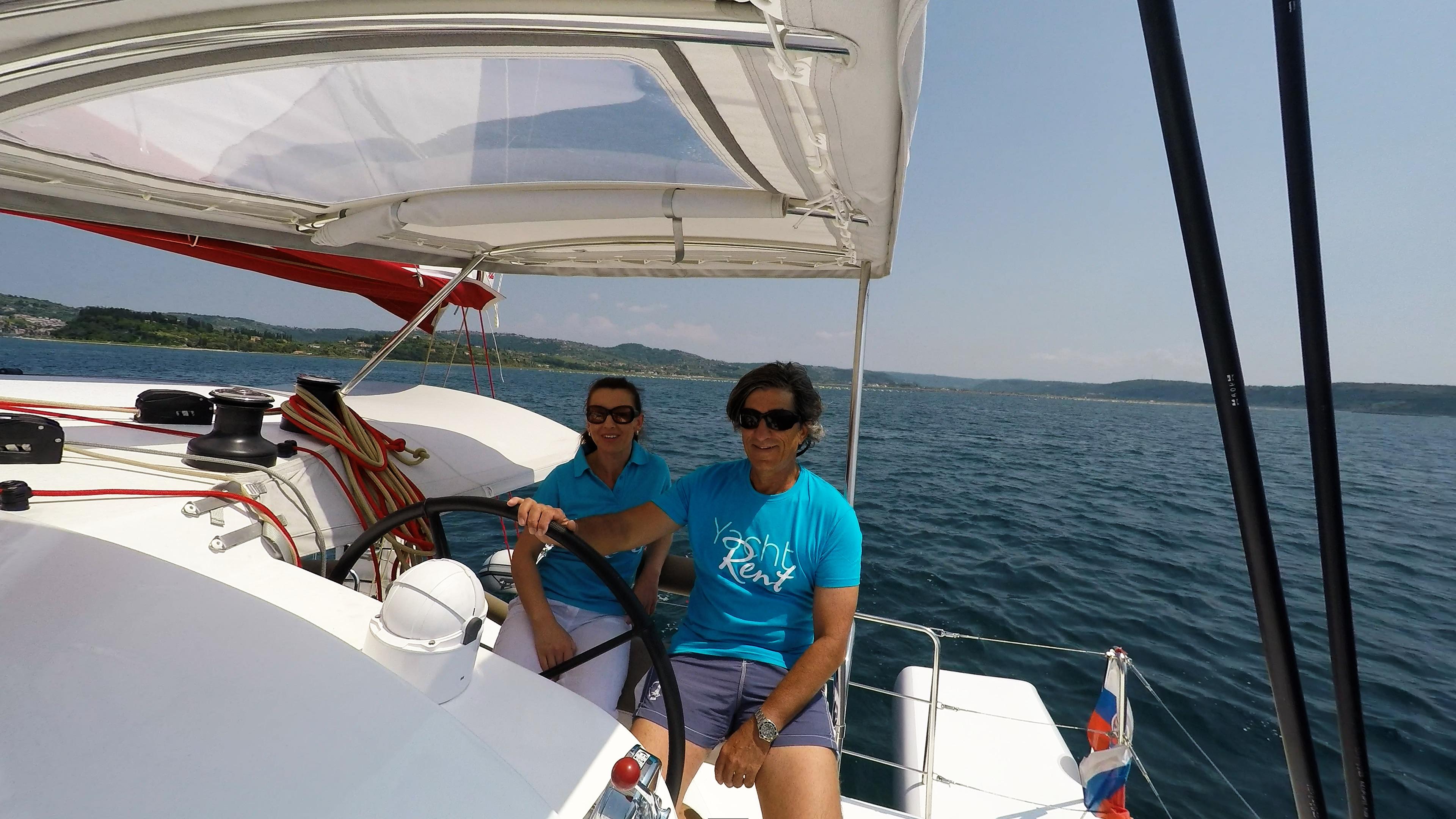 skipper e ragazza behind ruota del timone di trimarano  neel 45 yacht