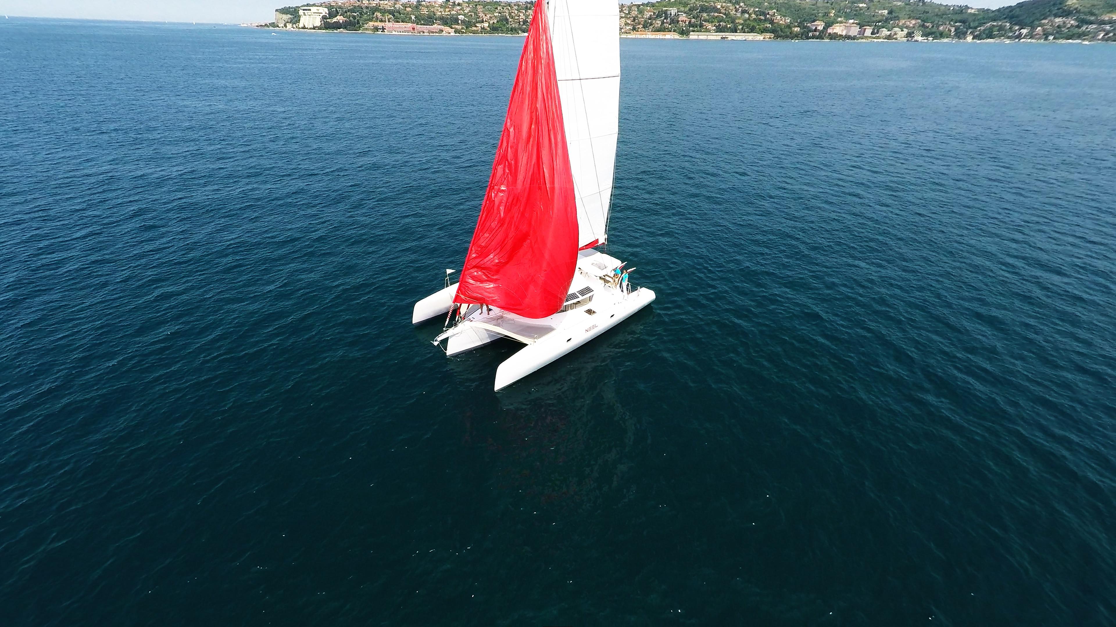 trimarano foto aerea hoisting rosso gennaker vela yacht