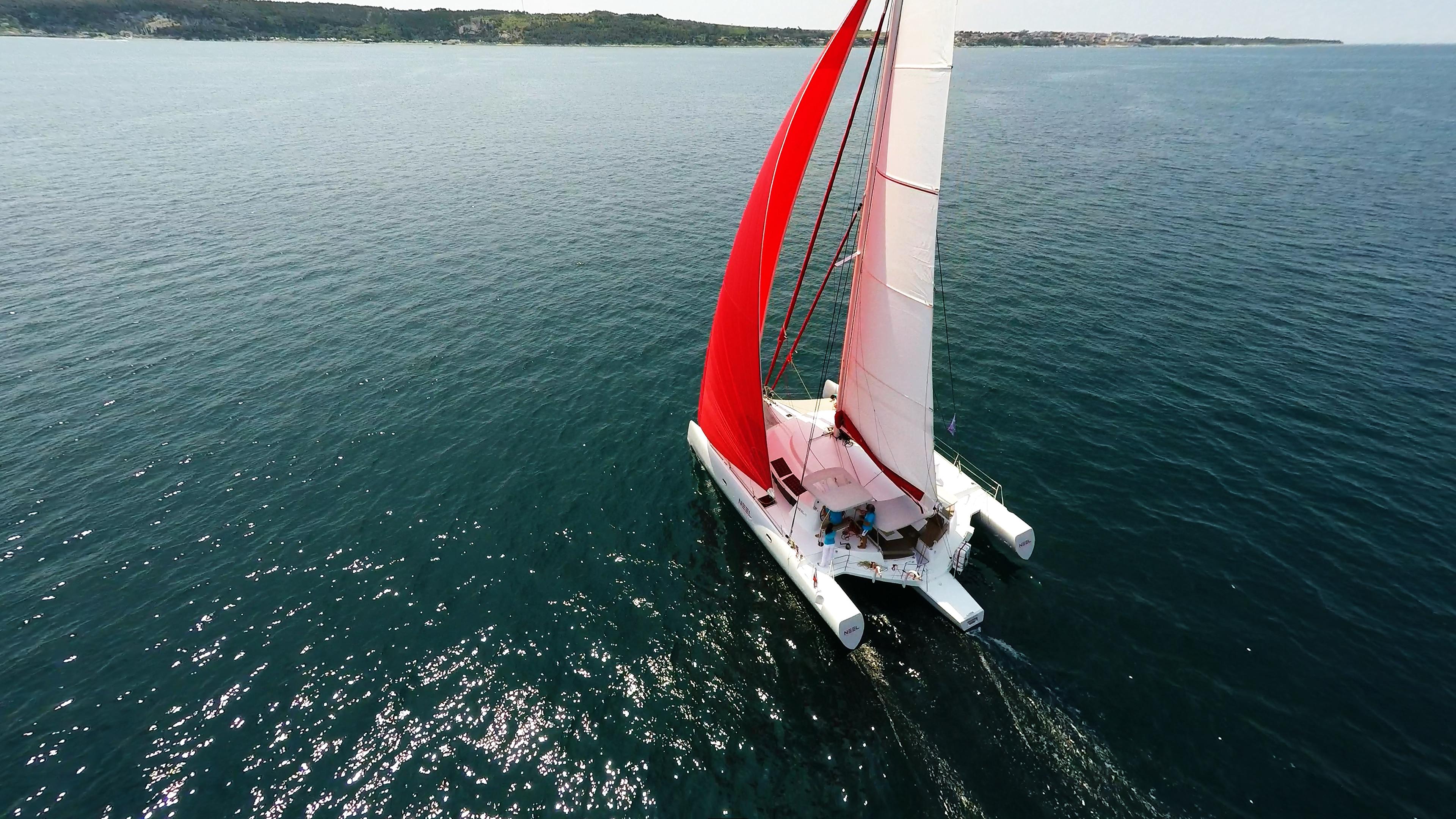 trimarano dall'alto rosso gennaker equipaggio in turchese magliette vela