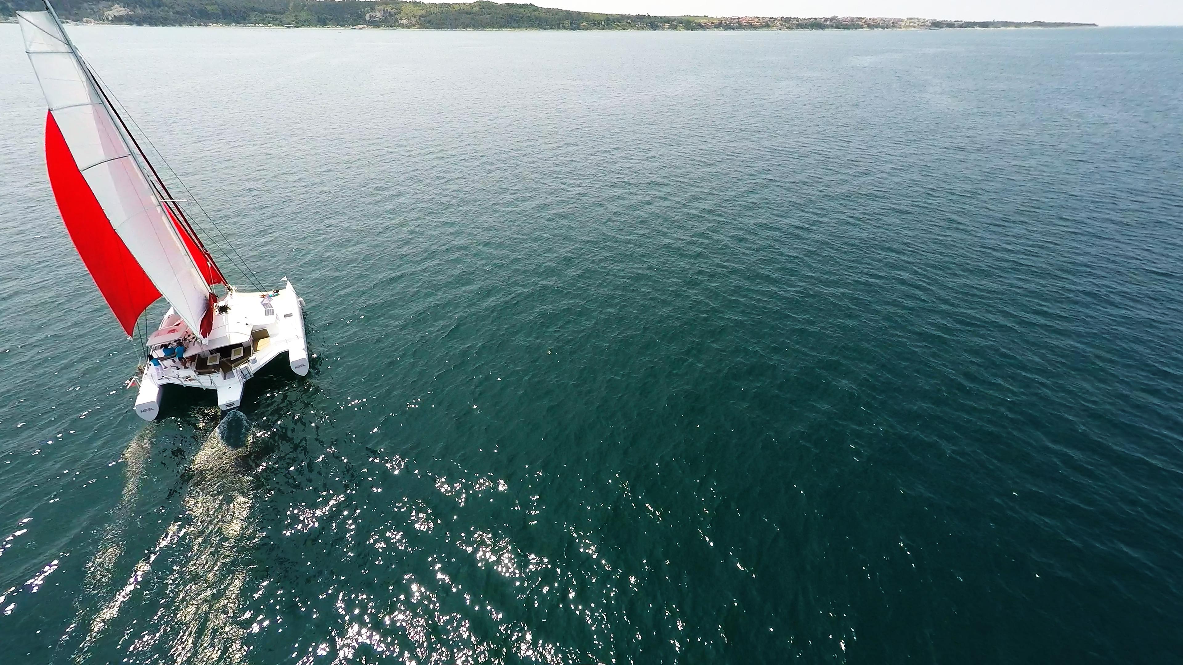trimarano naviga a vela al blu mare