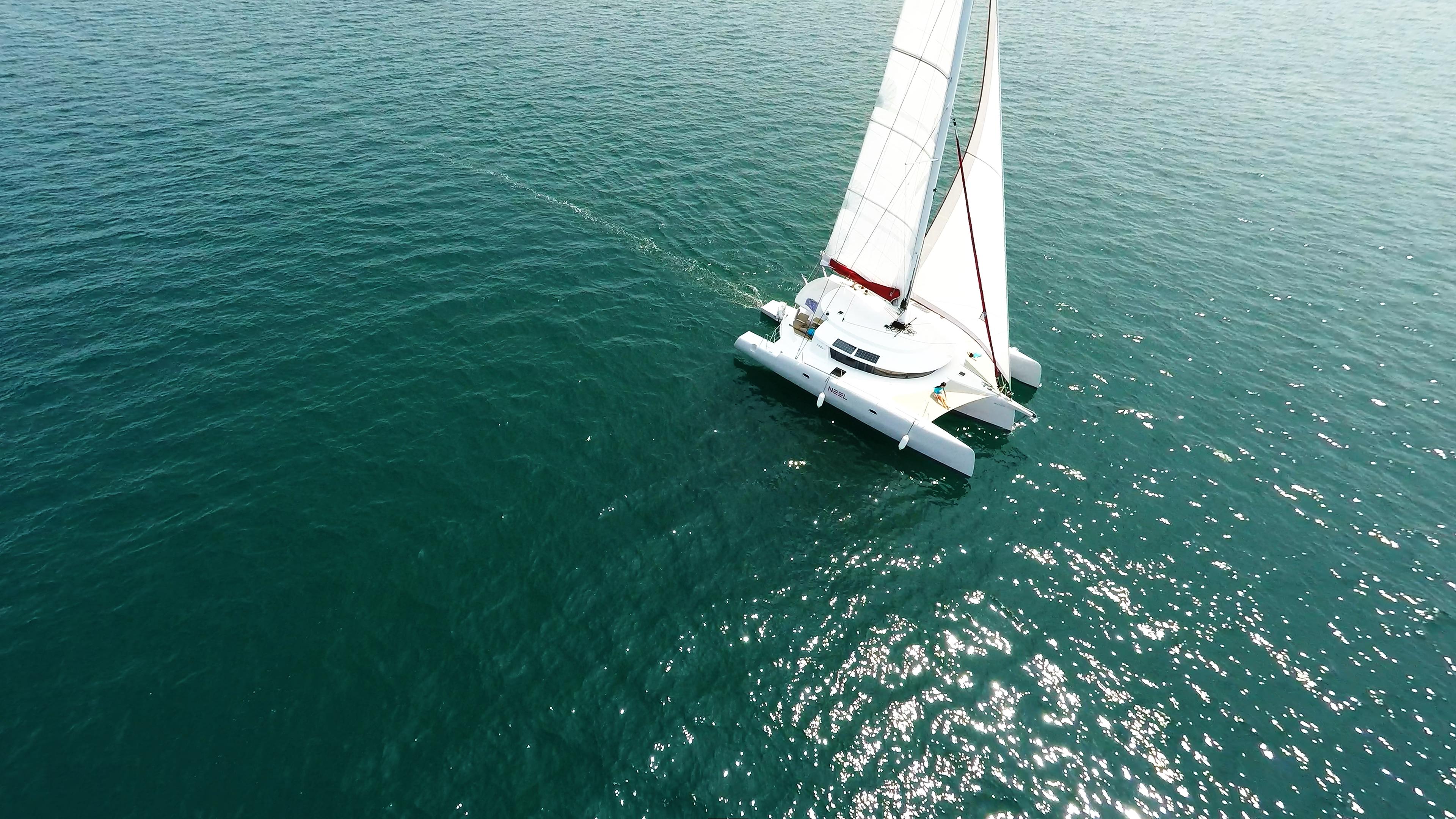 trimarano naviga a vela prendere il sole sul coperta