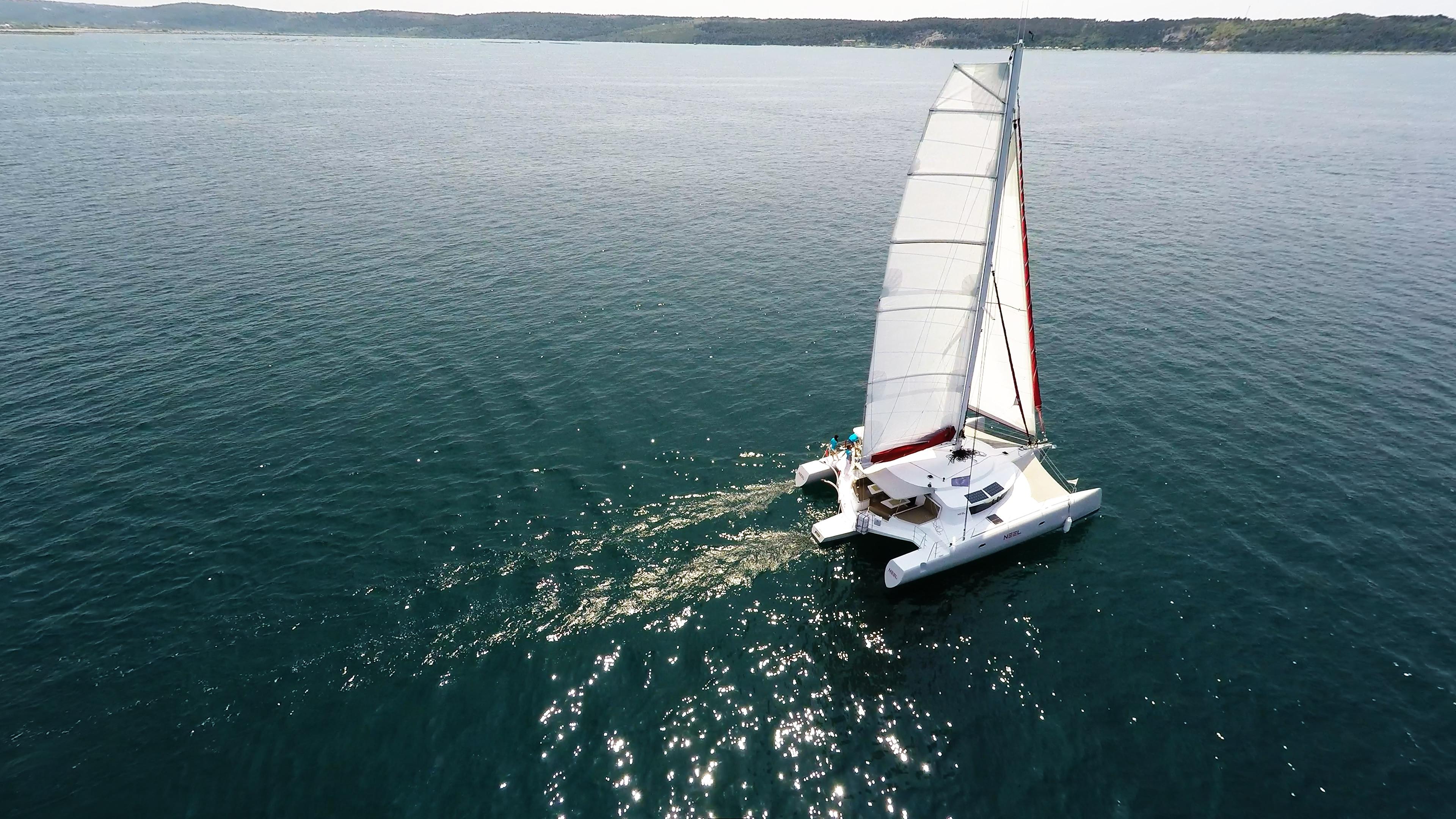 trimarano naviga a vela sole riflessa al mare