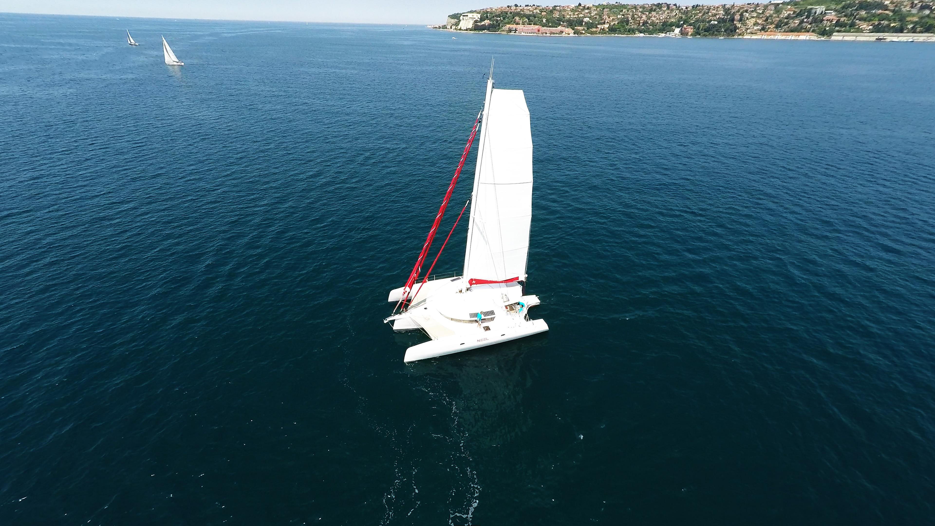 bianco trimarano yacht naviga a vela al blu mare